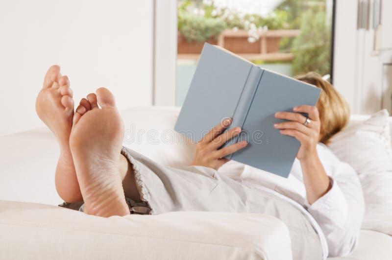 Кладущ ноги вверх и читать стоковые изображения rf