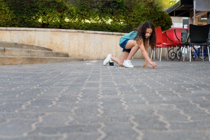 Классики девушки рисуя с мелом на спортивной площадке стоковое фото rf