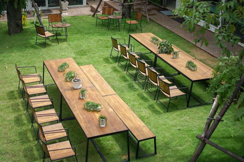 Классическая древесина со стальными таблицами оправы и стулья аранжированы в маленьком саде, сняли от 2-ого пола стоковая фотография rf