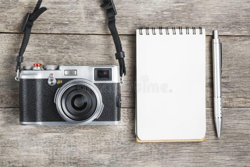 Классическая камера с пустой страницей блокнота и серая ручка на сером деревянном, винтажном столе стоковые изображения