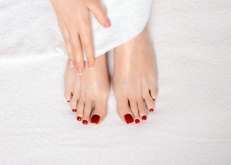 Классические красные pedicure и маникюр Женские ноги и рука на белом полотенце Terry, естественный тон кожи Женщина в салоне крас стоковая фотография rf