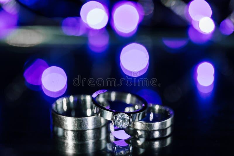 Классические свадьба белого золота и конец-вверх обручальных колец на влажной сверкная предпосылке Monochrome фото космоса экземп стоковое фото