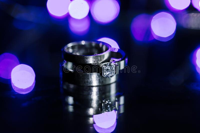 Классические свадьба белого золота и конец-вверх обручальных колец на влажной сверкная предпосылке Monochrome фото космоса экземп стоковое изображение rf