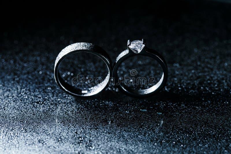 Классические свадьба белого золота и конец-вверх обручальных колец на влажной сверкная предпосылке Monochrome фото космоса экземп стоковые изображения rf