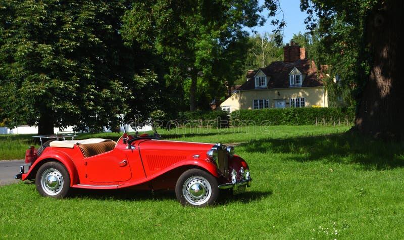 Классический автомобиль MG красного цвета припаркованный на зеленом цвете деревни стоковые фото