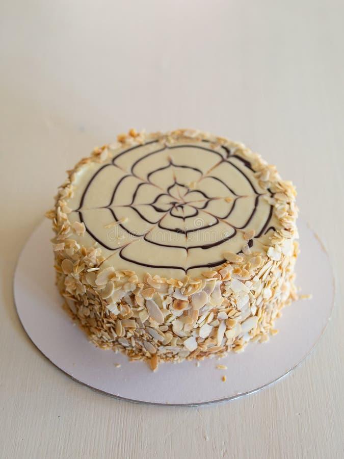 Классический торт Esterhazy украшенный с лепестками миндалины и паук шоколада на белой предпосылке стоковое фото