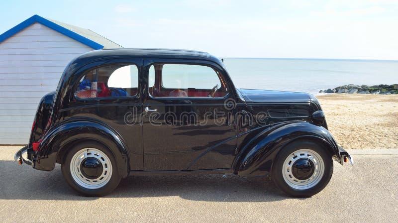Классическим черным припаркованная автомобилем прогулка набережной с хатой моря и пляжа в предпосылке стоковые фотографии rf