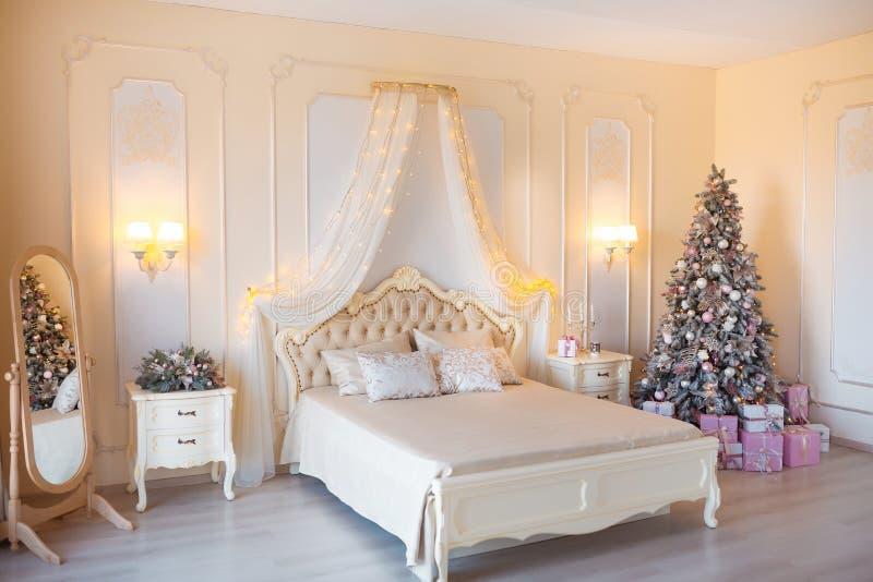 Классическое рождество украсило внутреннюю комнату с деревом Нового Года Современная роскошная спальня квартиры дизайна с кровать стоковые изображения