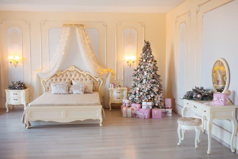 Классическое рождество украсило внутреннюю комнату с деревом Нового Года Современная роскошная спальня квартиры дизайна с кровать стоковое фото