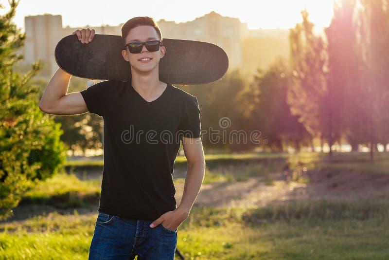 Классный парень в солнцезащитных очках, джинсах и черной футболке, позирующий с скейтбордом в летнем парке стоковое изображение