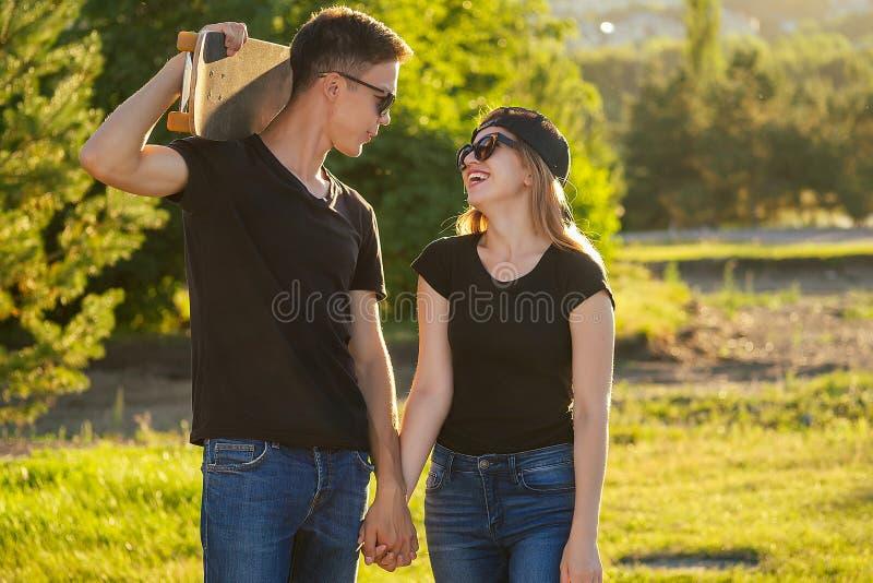 Классный парень и красивая девушка в солнцезащитных очках, джинсах и черной футболке, держащей руки на скейтборде в летнем парке стоковые фотографии rf