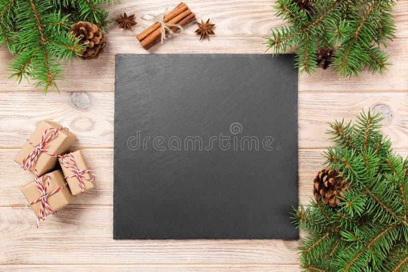 Классн классный шифера на деревянном столе с украшением рождества Черный камень шифера на деревянной предпосылке скопируйте космо стоковые фото