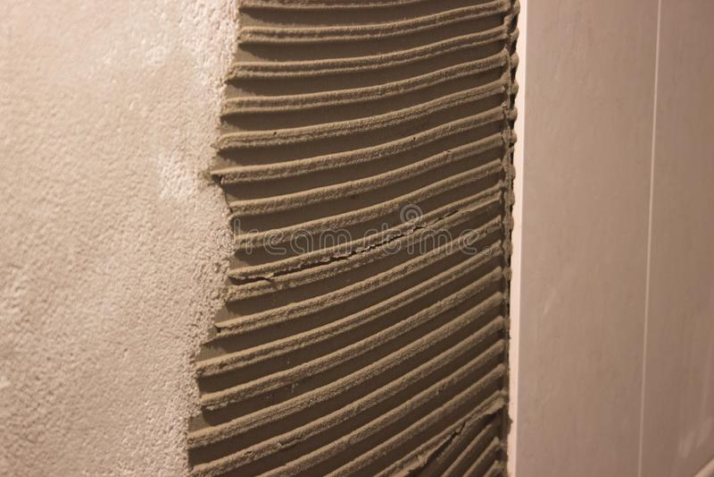 Класть керамические плитки на цементный раствор распределение решения вычисляло шпатель на стене работая процесс, tiler работы стоковые фотографии rf