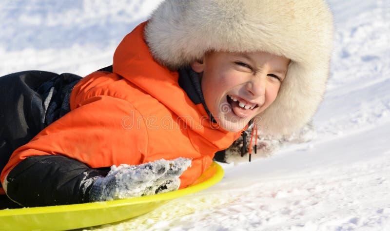 Класть мальчика усмехаясь на его скелетон, портрет конца-вверх управлять зимой розвальней потехи стоковое фото