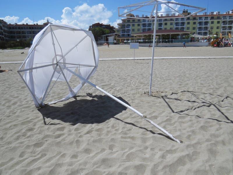 Класть разрушенный зонтик парасоля пляжа с белым песком в ветре защищая от Солнця во время экзотических каникул, Tsarevo, залив с стоковые фотографии rf