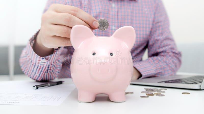 класть человека монетки банка piggy стоковые фотографии rf