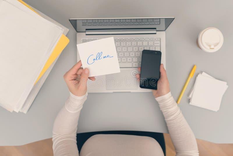 Клерк женщины в офисе держа стикер бумаги со словом вызывает меня r стоковые изображения