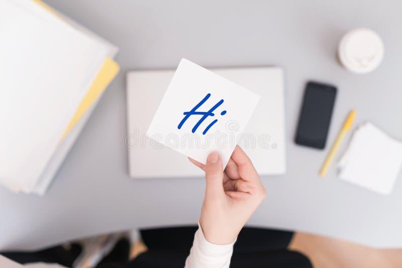 Клерк женщины сидя держащ стикер бумаги примечания с hi словом r стоковое фото rf