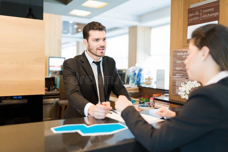 Клерк и предприниматель стоя на счетчике в лобби гостиницы стоковое фото