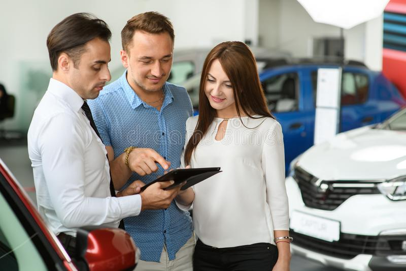 Клиенты выбирают варианты автомобиля на таблетке стоковая фотография rf