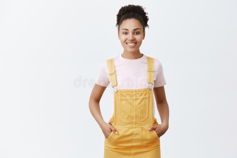 Клиенты приятного милого женского темнокожего работника помогая найти правый деталь для того чтобы купить Радостная выглядящая др стоковые фото