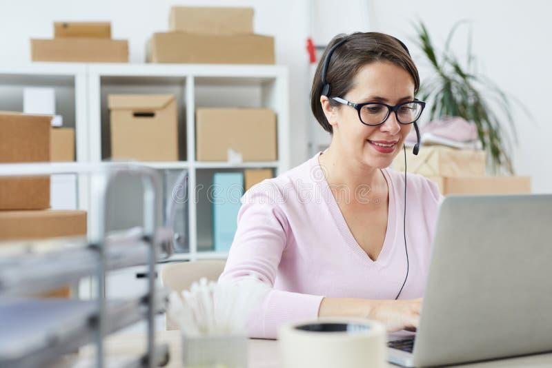 Клиенты счастливого оператора справочного бюро советуя с онлайн стоковое изображение