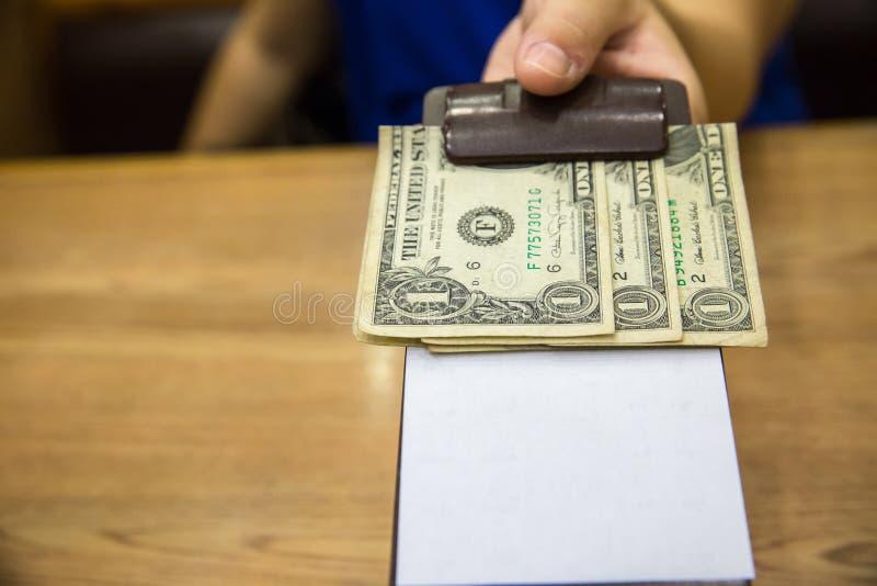 Клиент вручил наличные деньги на бумаге счета Банкнота доллара США наклоняет в кожаном черном получении счета стоковая фотография