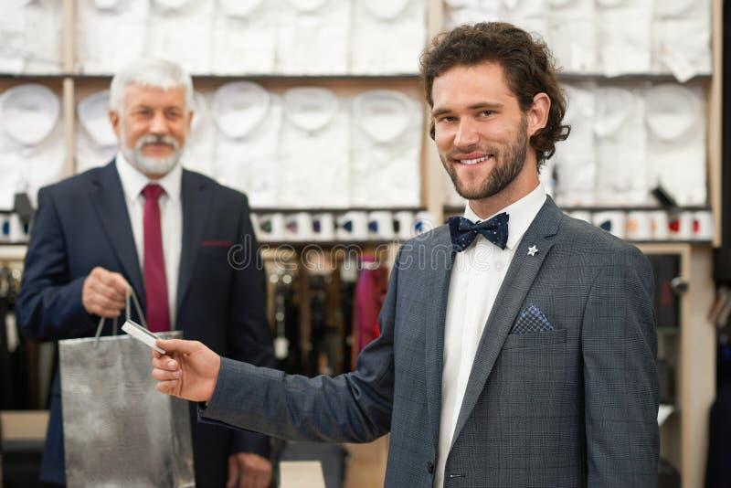 Клиент в черном костюме на детале ходя по магазинам покупки в бутике стоковая фотография