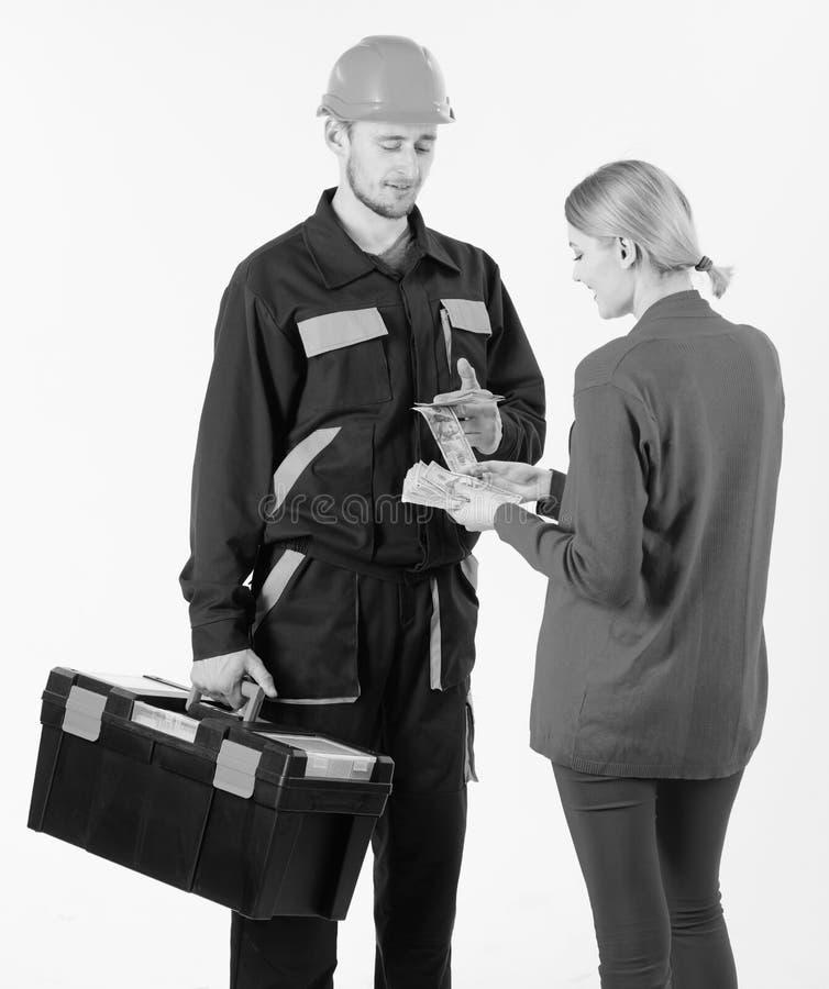 Клиент дает деньги к ремонтнику, построителю, механику с toolbox Repairer получает зарплату для работы День зарплаты и оплата стоковые изображения