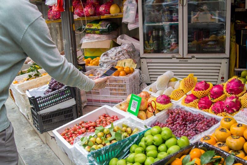 Клиент использует умный телефон для того чтобы оплатить на стойке рынка плода с кодом Qr стоковое фото rf