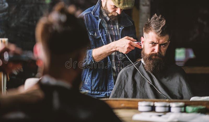 Клиент хипстера получая стрижку Парикмахер с клипером уравновешивая волосы на затылке клиента Концепция стиля причесок хипстера b стоковое фото rf