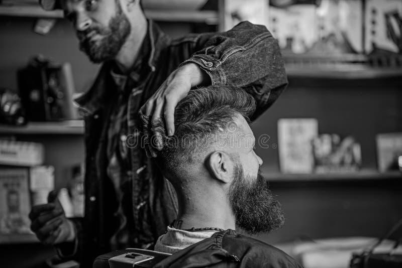 Клиент хипстера со свежими стрижкой или стилем причесок Парикмахер вводя волосы в моду бородатого клиента с воском руками Человек стоковое изображение rf