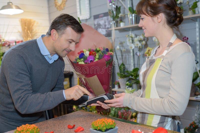 Клиент цветочного магазина оплачивая заказ стоковая фотография