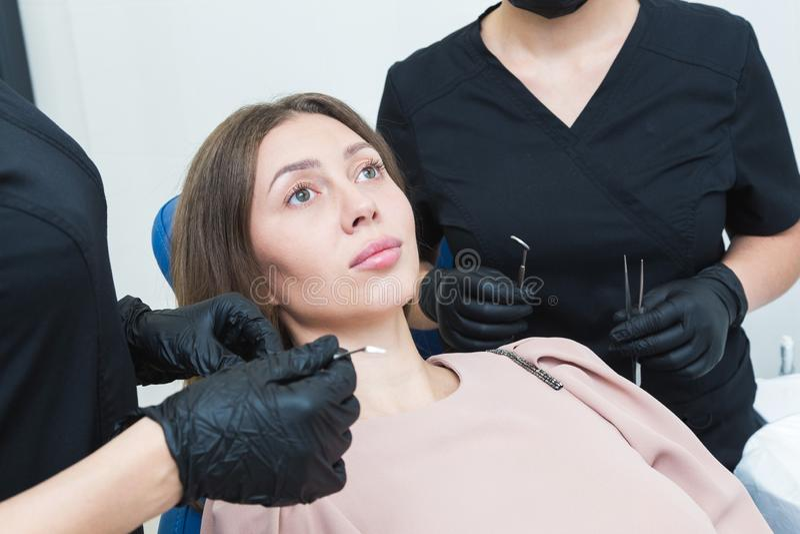 клиника зубоврачебная Прием, рассмотрение пациента Забота зубов Молодая женщина проходит зубоврачебное рассмотрение a стоковые фотографии rf