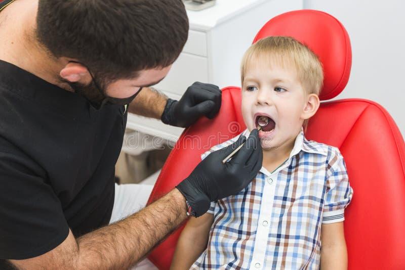 клиника зубоврачебная Прием, рассмотрение пациента Забота зубов Дантист обрабатывая зубы мальчика в офисе дантиста стоковое изображение