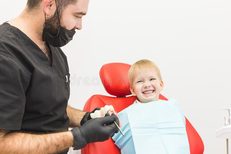 клиника зубоврачебная Прием, рассмотрение пациента Забота зубов Мужской дантист в зубоврачебном офисе разговаривая с пациентом стоковые фото