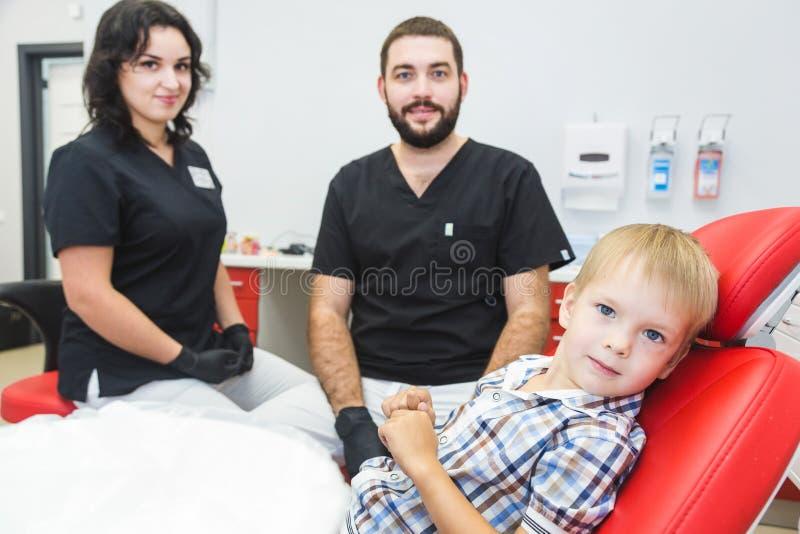 клиника зубоврачебная Прием, рассмотрение пациента Забота зубов Дантист обрабатывая зубы мальчика в офисе дантиста стоковая фотография rf