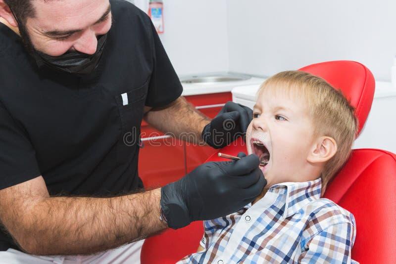 клиника зубоврачебная Прием, рассмотрение пациента Забота зубов Дантист обрабатывая зубы мальчика в офисе дантиста стоковое фото