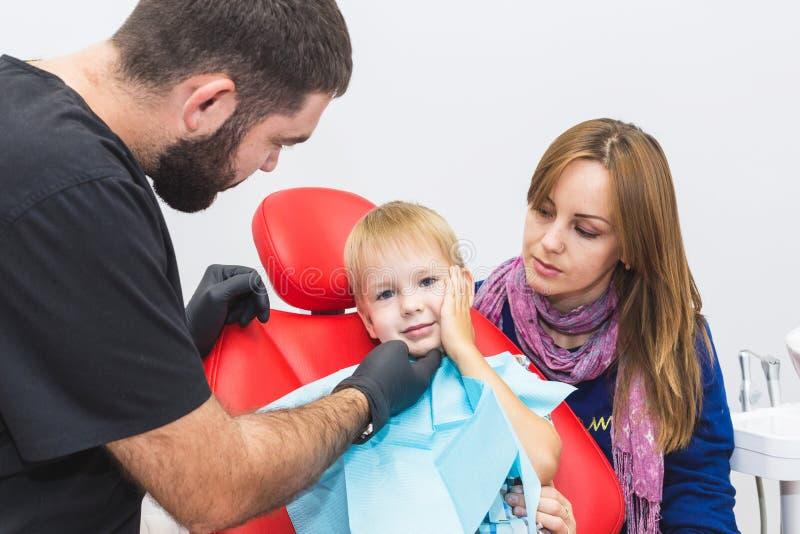 клиника зубоврачебная Прием, рассмотрение пациента Забота зубов Дантист обрабатывая зубы мальчика в офисе дантиста стоковое изображение rf