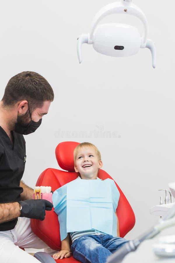 клиника зубоврачебная Прием, рассмотрение пациента Забота зубов Мужской дантист в зубоврачебном офисе разговаривая с пациентом стоковое фото
