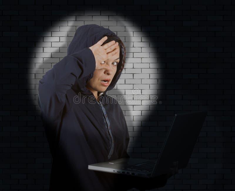 Клобук уголовного хакера женщины нося на использовании острословия Catched компьтер-книжки стоковые фотографии rf