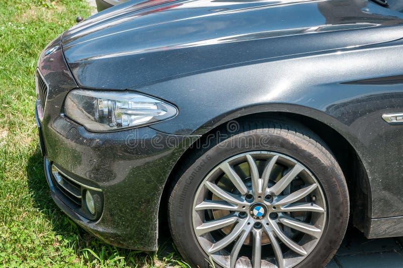 Клобук фары и автошина черного автомобиля серии 7 BMW припарковали на улице стоковые фотографии rf