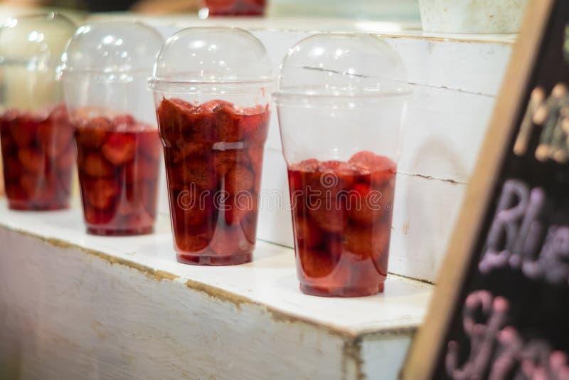 Клубника и сироп в пластиковом стеклянном шоу на полке подготавливают для сделанный к smoothies стоковое фото rf
