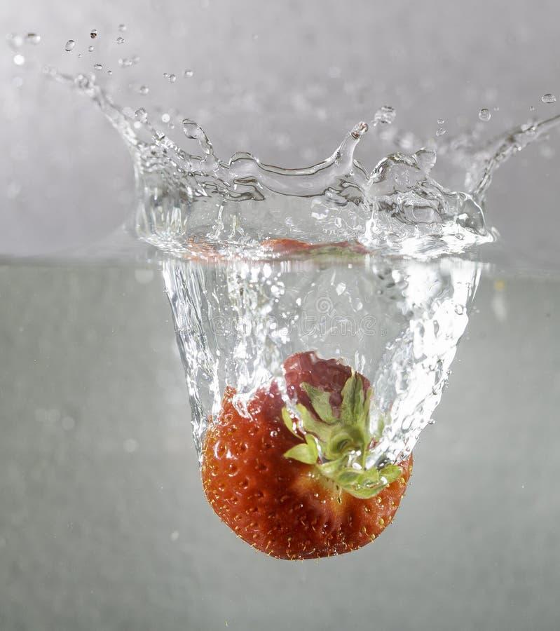 Клубника упала в консервную банку воды стоковая фотография