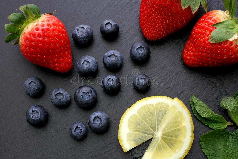 Клубники, куски лимона, листья мяты и голубики на черной предпосылке шифера стоковое фото