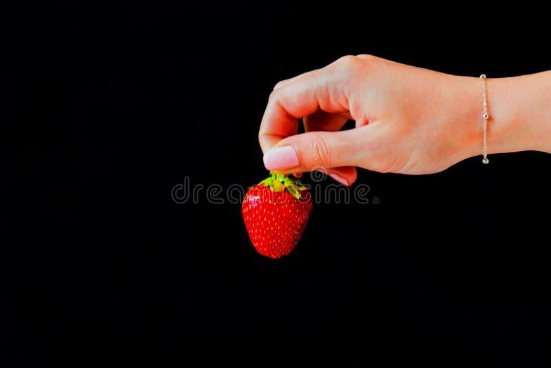 Клубники на черной предпосылке в руке девушки стоковая фотография rf