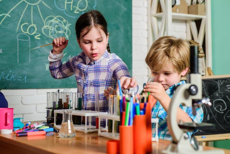 Клуб школы Объяснять химию для того чтобы оягниться Завораживающая химическая реакция Учитель и зрачки с пробирками в классе стоковая фотография rf