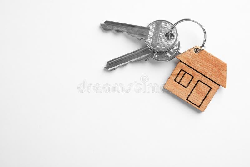 Ключи дома с побрякушкой на белой предпосылке, взгляде сверху стоковая фотография