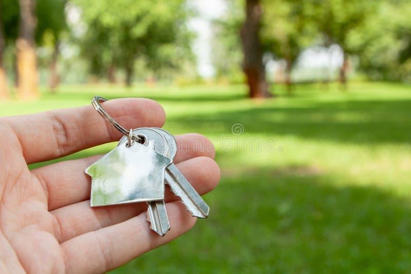 Ключи и дом keychain против предпосылки зеленой травы и парка стоковые изображения rf