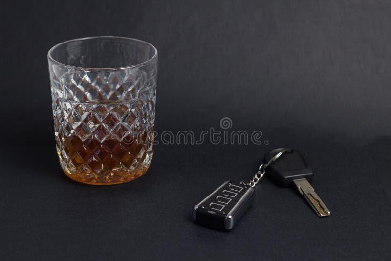 Ключи и стекло автомобиля с вискиом спирта на черной предпосылке, конце-вверх стоковые фотографии rf